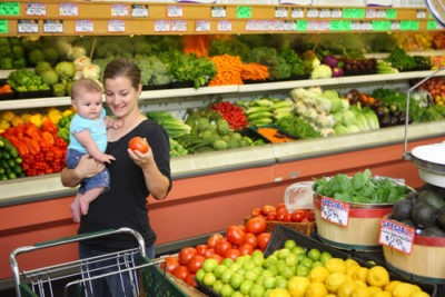 mother with baby picks produce